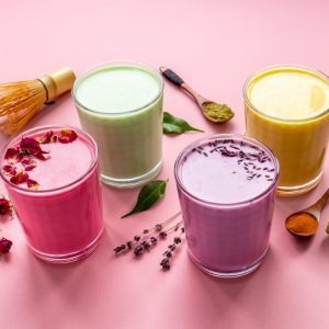 Green, yellow and pink latte. Hot colorful coffee or tea with milk